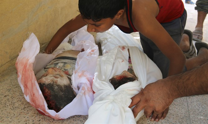 A Syrian boy mourns his brother and sister after they were killed during fighting in Aleppo, Syria