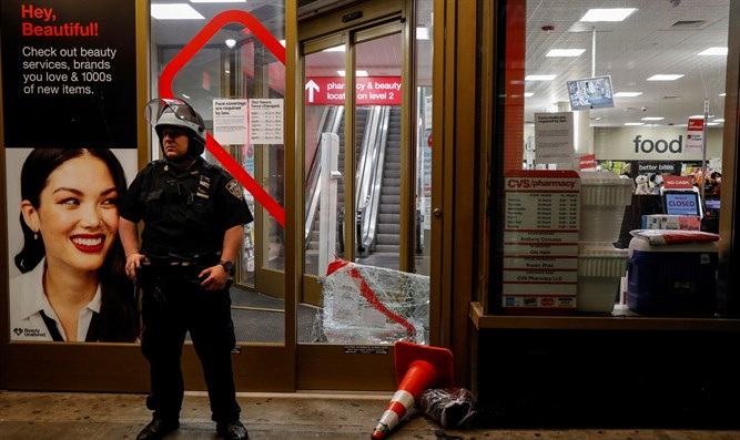Police officer outside NYC store after it was vandalized following George Floyd's death.