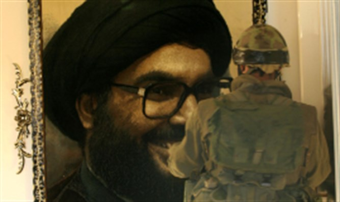 IDF soldier looks at portrait of Nasrallah in Lebanese