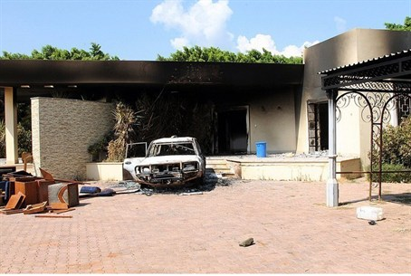 A burnt house and a car are seen inside the U