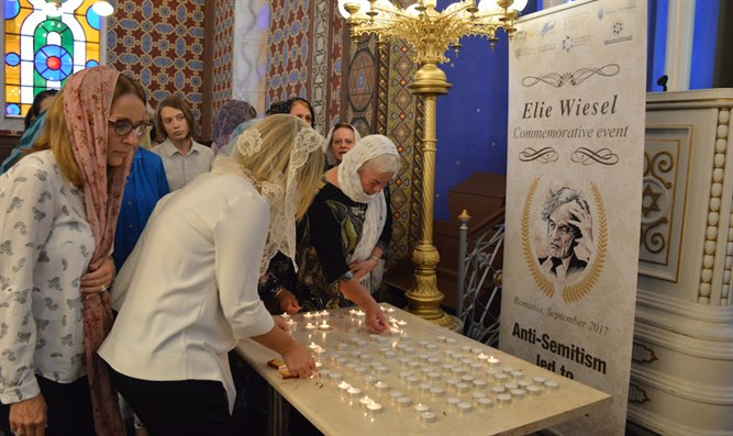 Women lighting a candle in memory of Elie Wiesel at the synagogue of Ordea in northern Rom