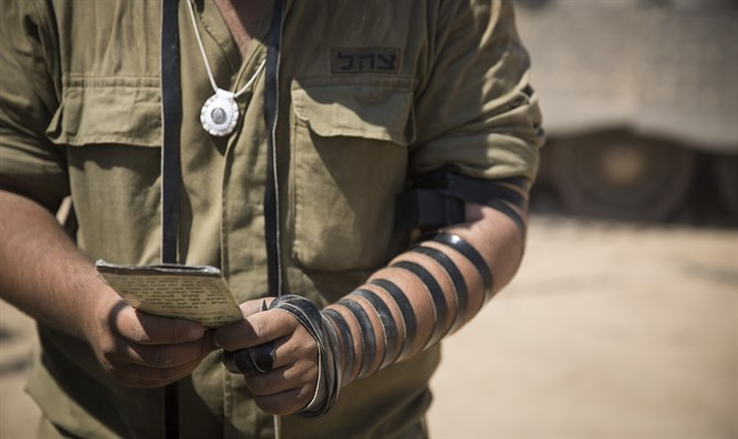 Israeli soldier prays while wearing tefillin at IDF staging area near Gaza